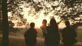 Kvinnor reser, går till och med skogen, beundrar landskapet på solnedgången Fotvandrareflicka handelsresande mamma och döttrar re stock video