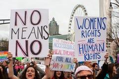 Kvinnor rymmer upp tecken på den Atlanta mars för social rättvisa Arkivbild