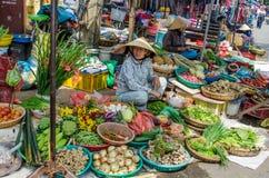 Kvinnor säljer nya frukter och grönsaker på en utomhus- marknad i kineskvarter Arkivfoton