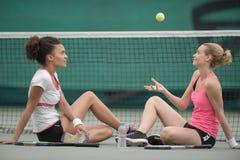 Kvinnor satt av den netto kasta bollen för tennisbanan in i luft Arkivfoton