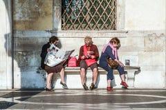 Kvinnor sitter på en bänk och läser tidningen och böcker Fotografering för Bildbyråer