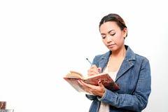 Kvinnor skriver i en bok Royaltyfri Bild
