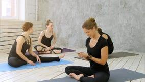 Kvinnor som öva yoga på den vård- klubban Unga flickor som talar och kopplar av efter kondition, yogainstruktör som använder smar Arkivbilder