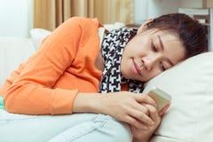 Kvinnor som använder en mobiltelefon i hem med det läs- meddelandet Royaltyfri Bild