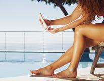 Kvinnor som applicerar solkräm på ben Royaltyfri Bild