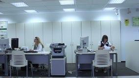 Kvinnor som arbetar i bankkontoret lager videofilmer