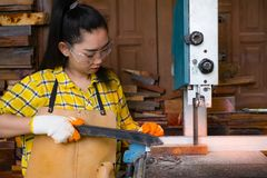Kvinnor som att stå är hantverket som arbetar klippt trä på en arbetsbänk med bandsågar, driver hjälpmedel på snickaremaskinen i  royaltyfri bild