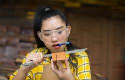 Kvinnor som att stå är hantverket som arbetar klippt trä på en arbetsbänk med bandsågar, driver hjälpmedel på snickaremaskinen i  royaltyfria foton