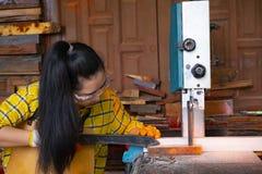 Kvinnor som att stå är hantverket som arbetar klippt trä på en arbetsbänk med bandsågar, driver hjälpmedel på snickaremaskinen i  fotografering för bildbyråer