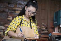 Kvinnor som att stå är hantverket som arbetar klippt trä på en arbetsbänk med cirkelsågar, driver hjälpmedel på snickaremaskinen arkivfoto