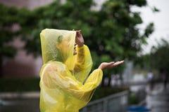 Kvinnor som bär den gula regnrocken, medan regna i regnig säsong royaltyfri bild