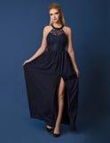 Kvinnor som bär den svarta eleganta klänningen på den blåa bakgrunden royaltyfria bilder