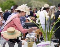 Kvinnor som bär hatten på ett bakluckaparti på hästkapplöpningen Arkivbild