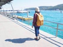 Kvinnor som bär jeans och den röda plädskjortan och vandrar guling som gör att gå på bron, ser havet royaltyfria foton