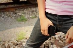 Kvinnor som bär jeans som rymmer en mobiltelefon royaltyfri fotografi
