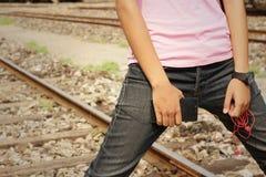 Kvinnor som bär jeans som rymmer en mobiltelefon royaltyfria foton