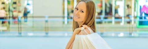 Kvinnor som bär många shoppa påsar i det suddiga shoppinggalleriaBANRET, LÅNGT FORMAT arkivbilder