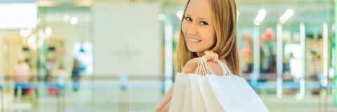 Kvinnor som bär många shoppa påsar i det suddiga shoppinggalleriaBANRET, LÅNGT FORMAT fotografering för bildbyråer