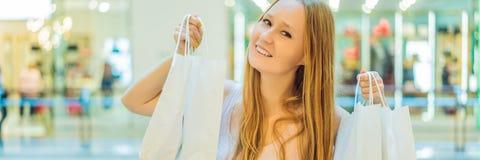 Kvinnor som bär många shoppa påsar i det suddiga shoppinggalleriaBANRET, LÅNGT FORMAT royaltyfria bilder