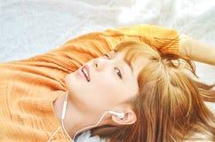 Kvinnor som bär orange skjortor, lyssnar till musik och är lyckliga arkivfoton
