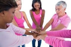 Kvinnor som bär rosa färger och band för bröstcancer som tillsammans sätter händer Arkivfoton