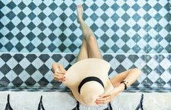 Kvinnor som b?r sugr?rhattar och, kopplar av i simbass?ngen fotografering för bildbyråer