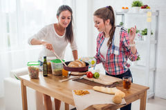 Kvinnor som bakar hemmastatt nytt bröd i kök Arkivbild