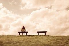 Kvinnor som bara sitter på en väntande på förälskelse för bänk Arkivfoto