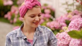 Kvinnor som bevattnar blommor Rosa härliga blommor Kvinnor att bry sig blommor just rained Lyckliga kvinnor i trädgård arkivfilmer