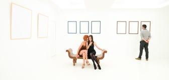Kvinnor som delar hemligheter i en konstgalleri Arkivbilder