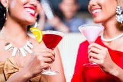 Kvinnor som dricker coctailar i utsmyckad stång Fotografering för Bildbyråer