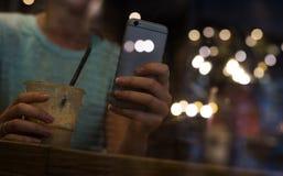 Kvinnor som dricker kaffe och använder den smarta telefonen i restaurang Arkivbild