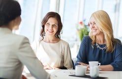 Kvinnor som dricker kaffe och talar på restaurangen Arkivfoto