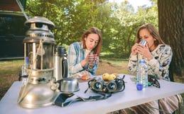 Kvinnor som dricker koppar kaffe i skog Royaltyfria Bilder