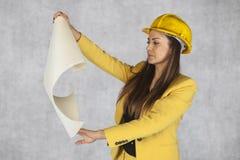 Kvinnor som en bärare ser byggnadsplan Arkivbild