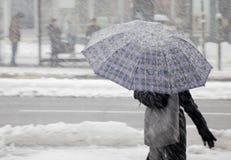 Kvinnor som en går under paraplyet i tungt snöfall fotografering för bildbyråer