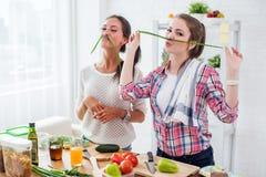 Kvinnor som förbereder sund mat som spelar med grönsaker i kök som har det roliga begreppet som bantar näring Arkivbild