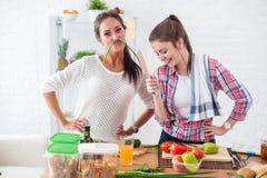 Kvinnor som förbereder sund mat som spelar med grönsaker i kök som har det roliga begreppet som bantar näring Royaltyfria Bilder