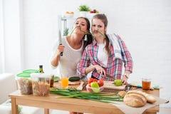 Kvinnor som förbereder sund mat som spelar med grönsaker i kök som har det roliga begreppet som bantar näring Fotografering för Bildbyråer
