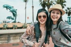 Kvinnor som framme tar selfies av delfinspringbrunnen royaltyfri fotografi