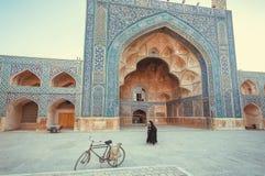 Kvinnor som går förbi en historisk persisk moské med härliga konstverk Arkivfoton