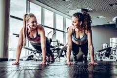 Kvinnor som gör den raka armplankan på grupputbildning i idrottshall arkivfoto