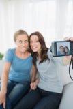 Kvinnor som gör framsidor, medan ta bilder av dem Royaltyfri Bild