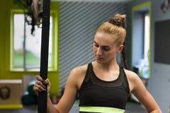 Kvinnor som gör handtag, ups utbildningsarmar med trxkonditionremmar i sporten för livsstilen för idrottshallbegreppsgenomköraren Royaltyfria Bilder