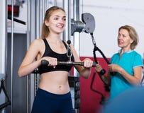 Kvinnor som gör powerlifting på maskiner Arkivbild