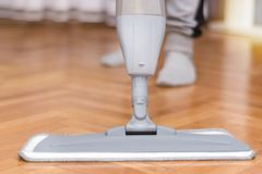 Kvinnor som gör ren golvparketten med grå golvmopp royaltyfria foton