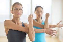 Kvinnor som gör sträcka övning på idrottshallen royaltyfri fotografi