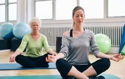 Kvinnor som gör yoga i grupp Fotografering för Bildbyråer