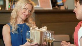 Kvinnor som ger gåva till vännen på vinstången arkivfilmer