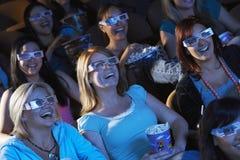Kvinnor som håller ögonen på filmen 3D i teater Royaltyfri Foto